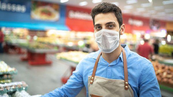 Grocery store employee wearing face mask and social distancing