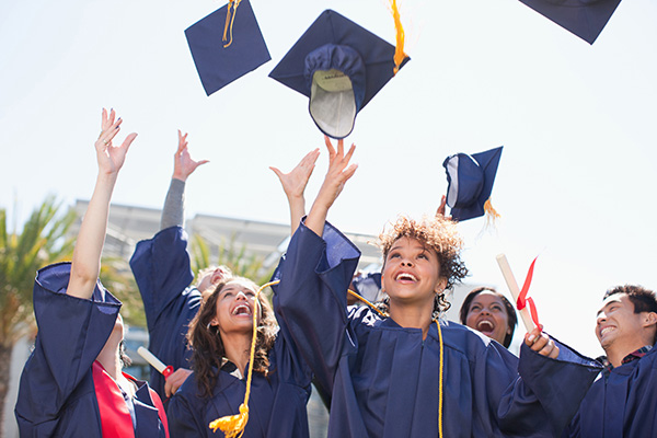 Image of high school graduates tossing mortarboards