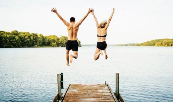 Couple jumping in lake.