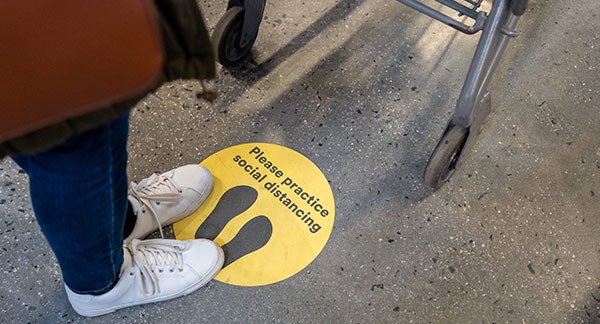 Please practice social distancing sticker on grocery store floor